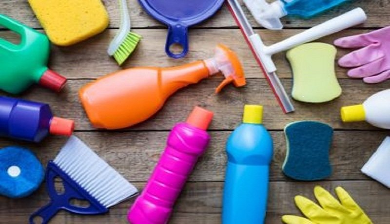 spray bottle, squeegee, sponge and rubber gloves on wooden surface