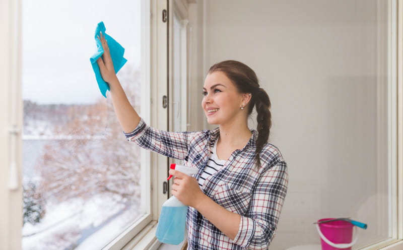 Happy woman wiping window glass with rag and holding spray bottle in hand