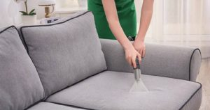 cropped image of woman vacuuming a couch