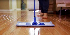 cropped image of a woman mopping hardwood floor