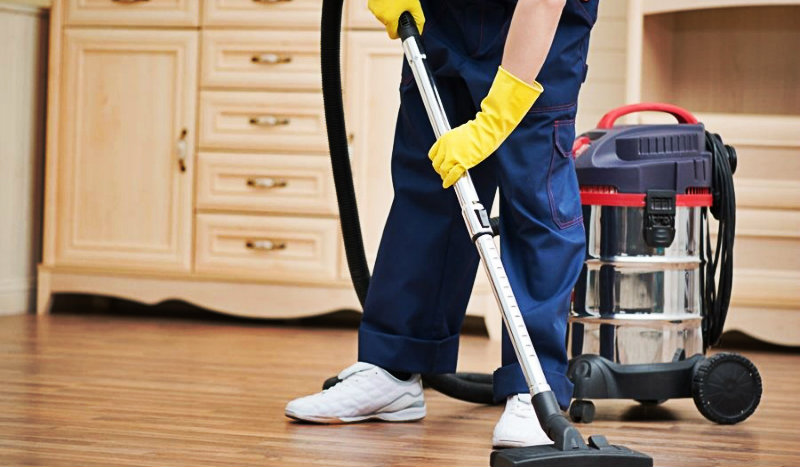 cropped image of a man vacuuming hardwood floor using professional equipment
