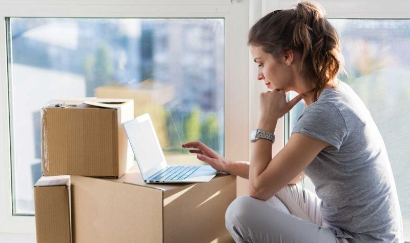 beautiful woman sitting on the floor with her laptop and some cardboard boxes