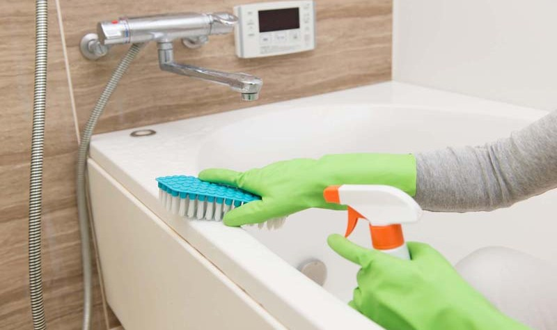 cropped image of a woman scrubbing a bathtub with a brush