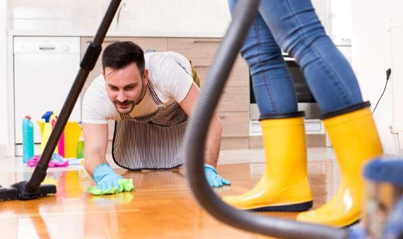 young man wiping the floor and woman vacuuming the floor