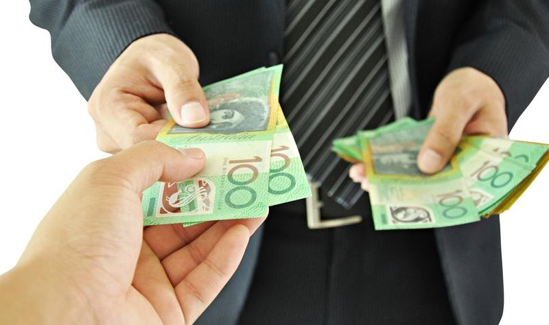 Cropped picture of two man exchanging Australian currency