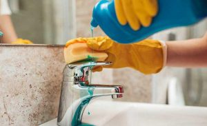cropped picture of a woman disinfecting bathroom basin tap