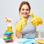 a happy woman with some scrubbers and spray bottle posing for a picture