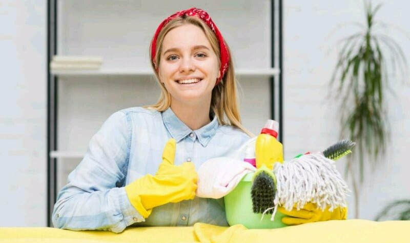 young beautiful woman holding a bucket full of cloth mops, spray bottles and brushes