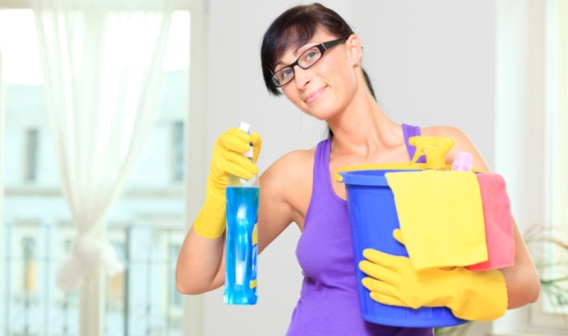 A woman holding a bucket and a spray bottle