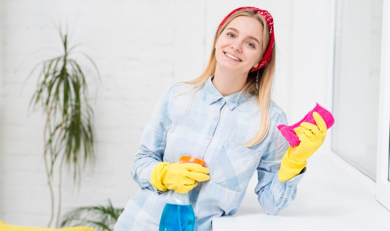 young woman with a spray bottle and a sponge posing for a picture