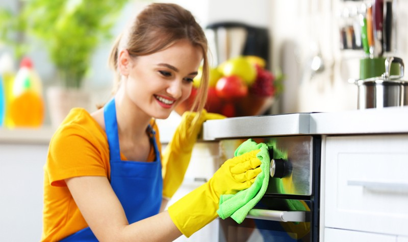 young woman wiping an oven