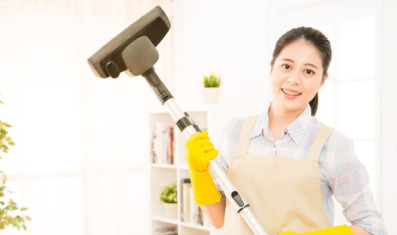 young woman holding a wiper and preparing to clean her house