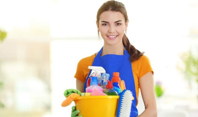 young professional holding a bucket full of spray bottles and brushes