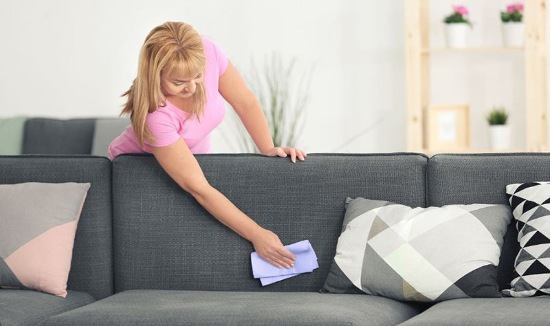 a woman wiping a couch with a cloth