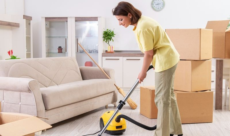 young woman vacuuming a room before moving out
