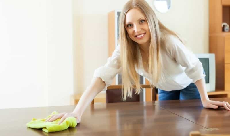 woman with blonde hairs wiping a wooden surface