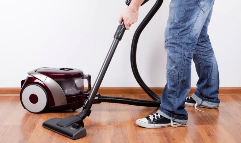 cropped picture of a man vacuuming the floor