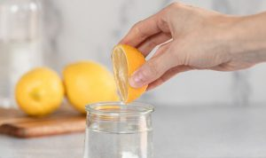 cropped picture of a woman squashing lemon in a glass