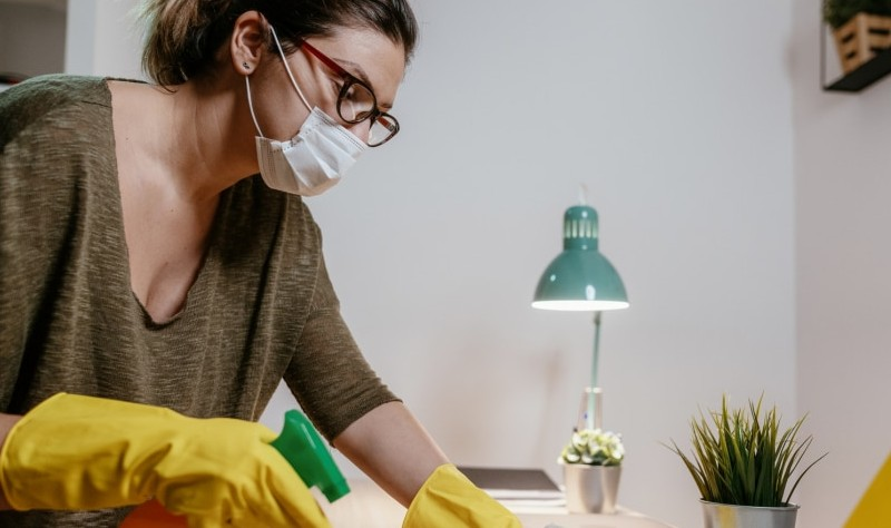 young woman wearing a mask disinfecting a house