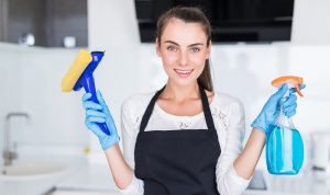 young woman holding a brush and spray bottle posing for a picture